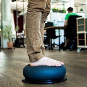 Dynamisches Stehen mit einem Balance-Kissen für Steharbeitsplätze